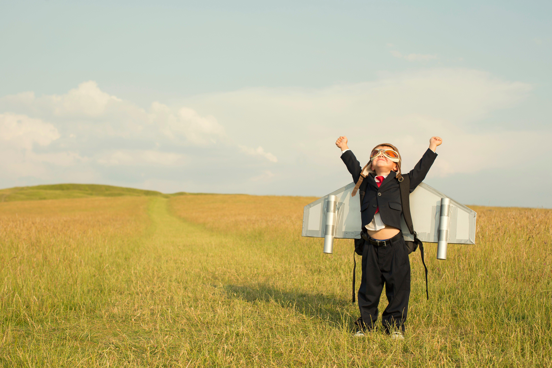Offene Stellen. Stimmungsbild eines Kinds, dass sich mit Flügel auf dem Rücken zum Himmel streckt. Bei Project Competence sind die Chancen grenzenlos.
