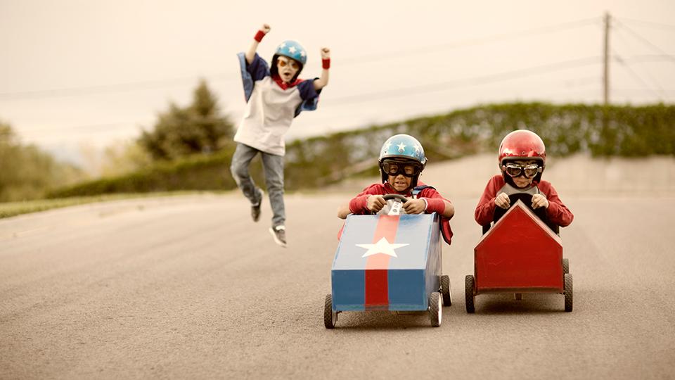 Beratung: Stimmungsbild von zwei Kindern die ein Seifenkistenrennen Fahren zur Illustration der erfolgreichen Beratung der Beraterinnen und Berater von Project Competence